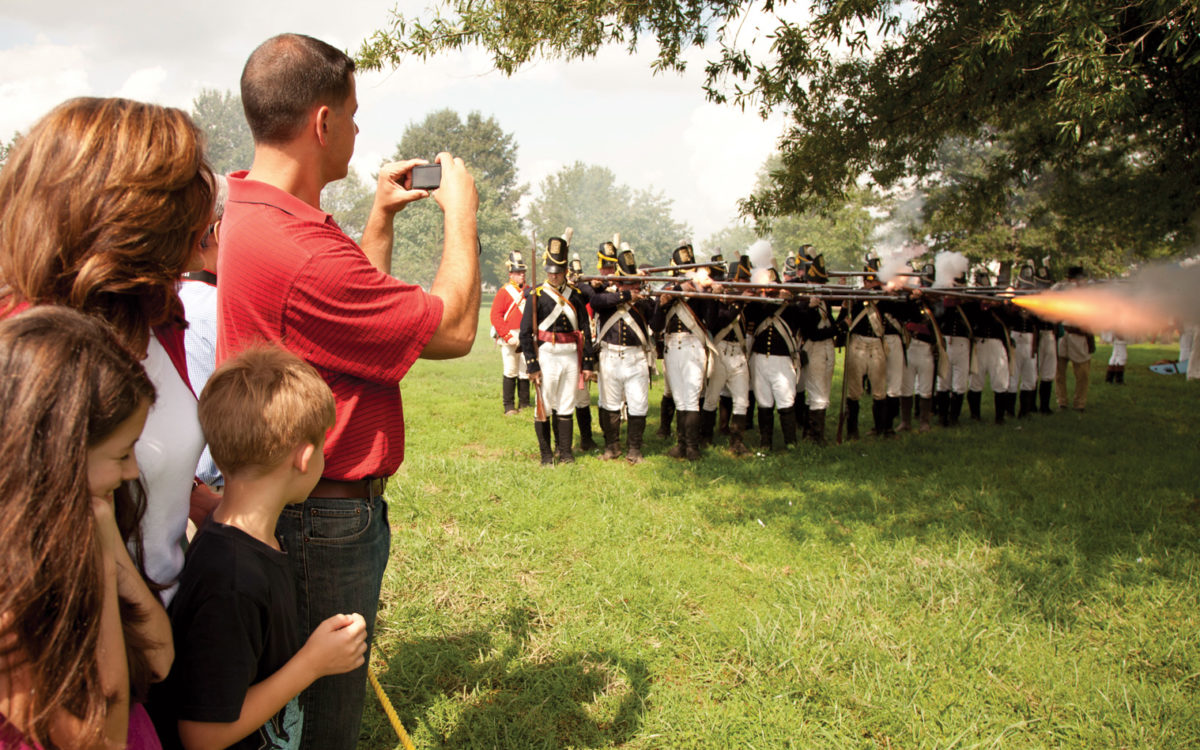 Person taking a photograph of marchers at Fort McHenry.
