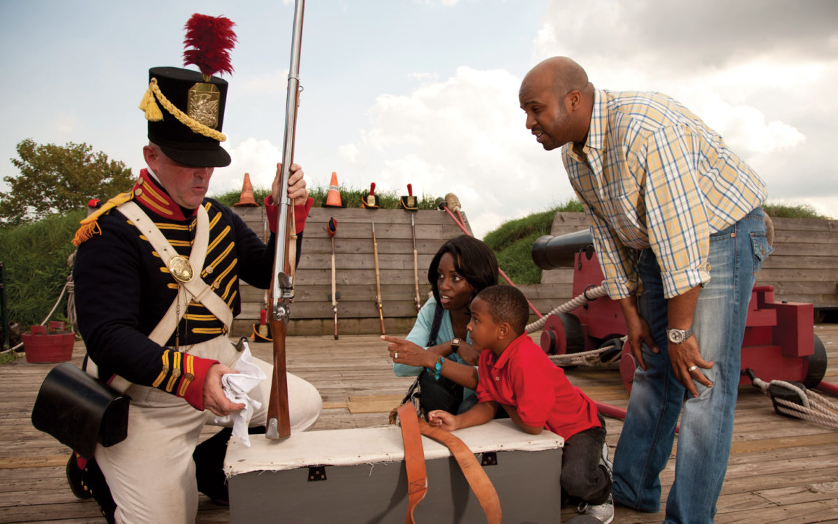 People interact with a marcher behind the ramparts of Fort McHenry.