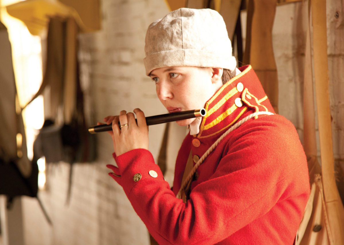 A farb plays the flute behind the ramparts of Forth McHenry.