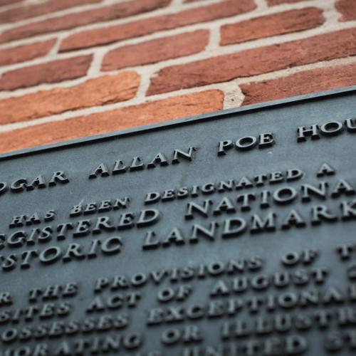 A close up of Edgar Allen Poe House plaque.