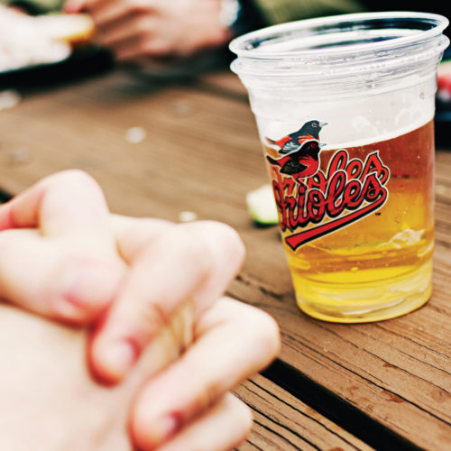 Hands clasped at a table with beer at Camden Yards.
