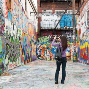 A woman shooting an image at Graffiti Alley in Station North.