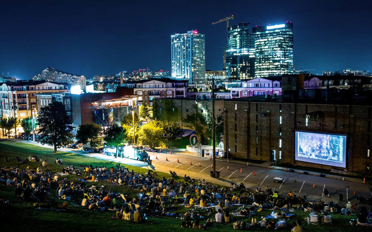 Folks watch movies on the hill at night at AVAM in Baltimore.
