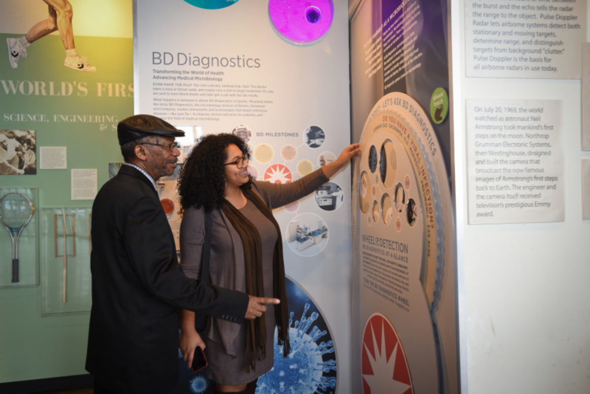 Woman and man interacting with a wheel on an exhibit.