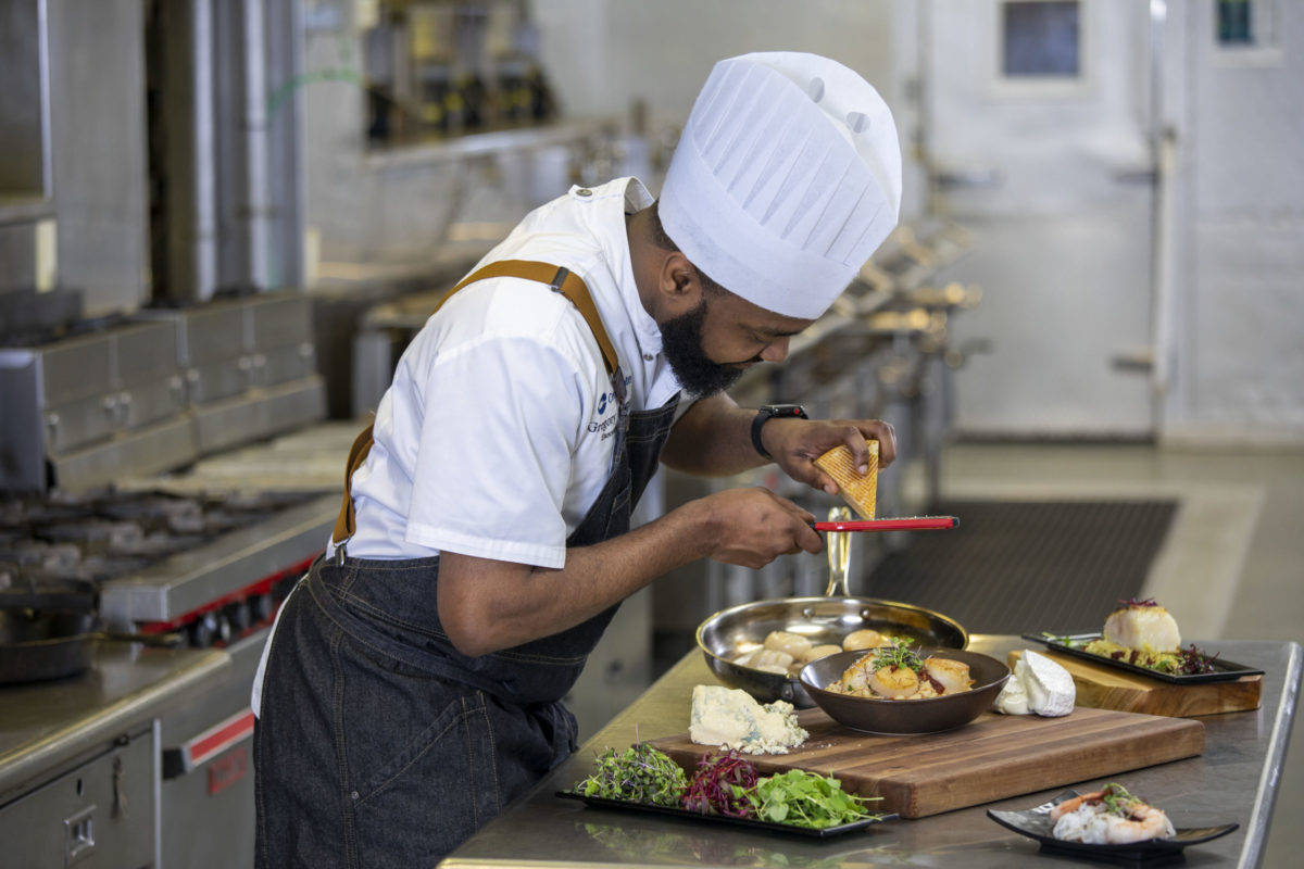 Executive Chef Gregory Pittman grates cheese over a dish at Centerplate