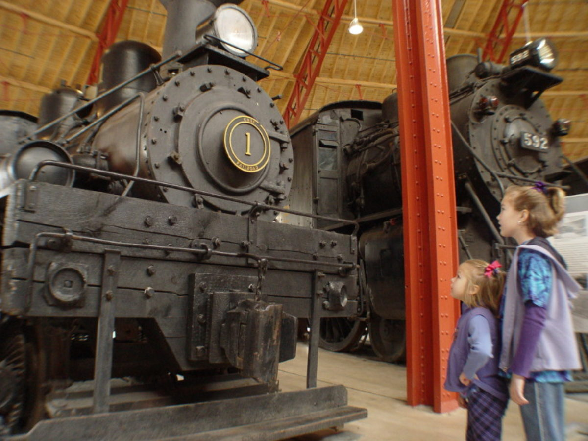 Two small children looking at the front of a black steam train.