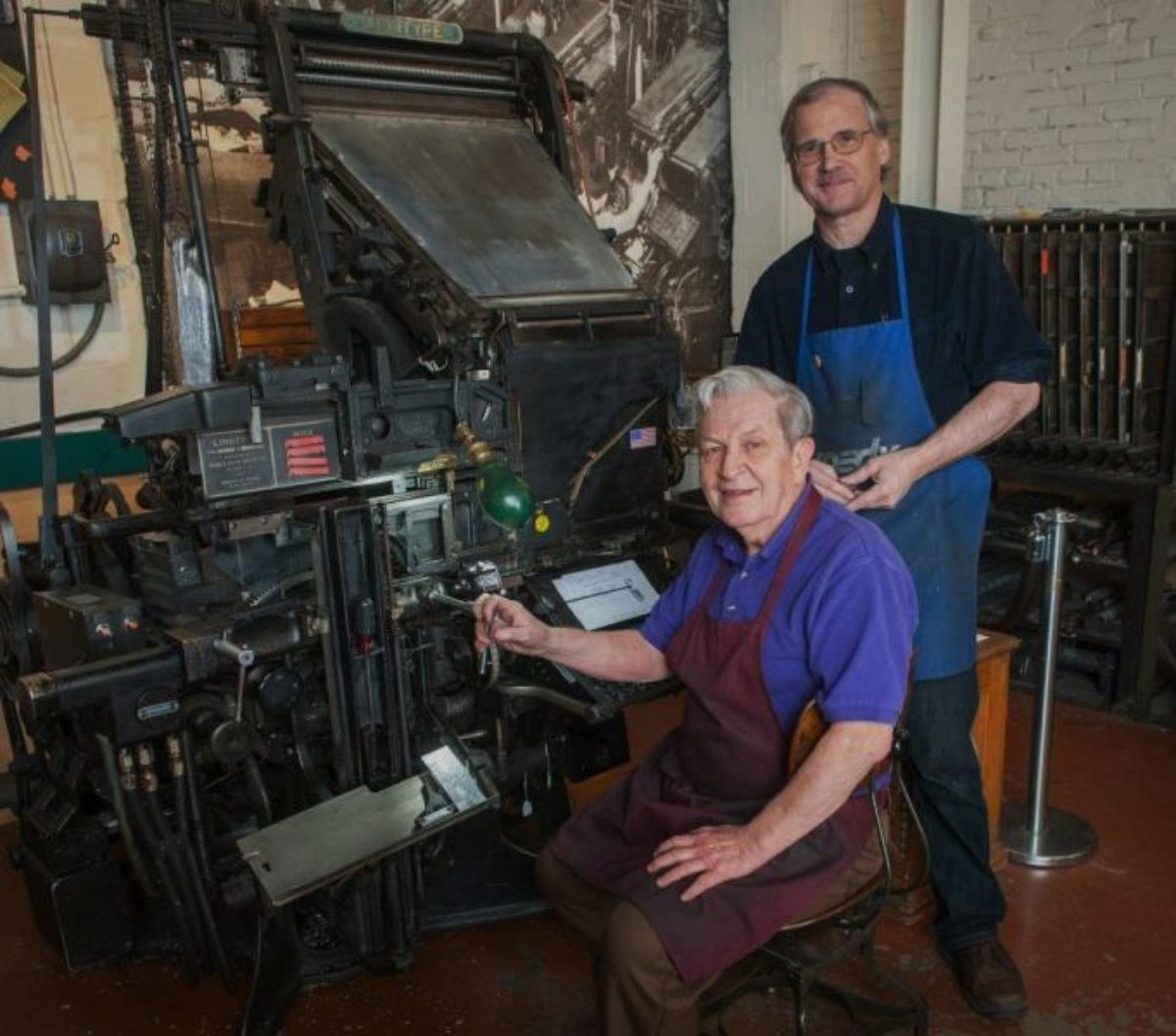 Two men in aprons posing by linotype press.
