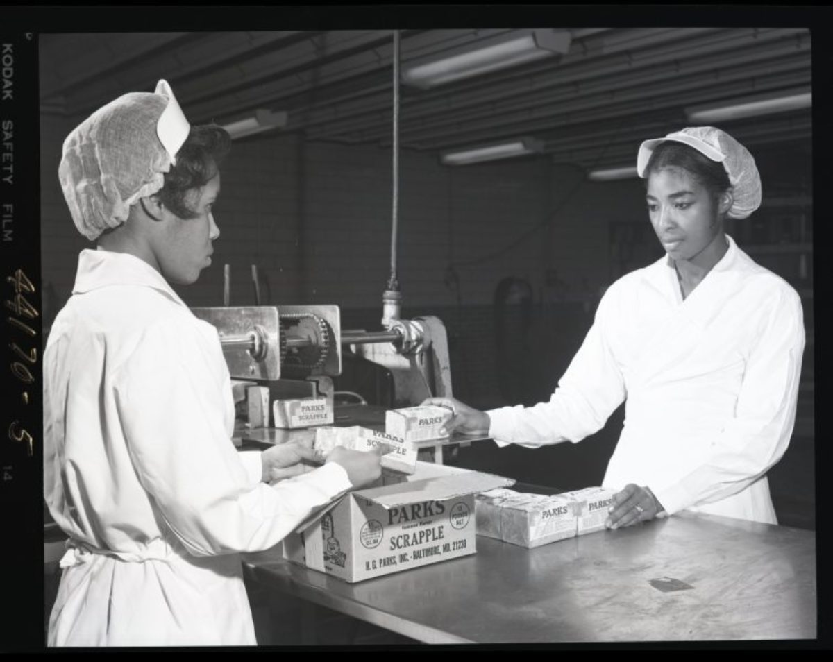 Vintage black and white photo of two women packing a box at a sausage factory