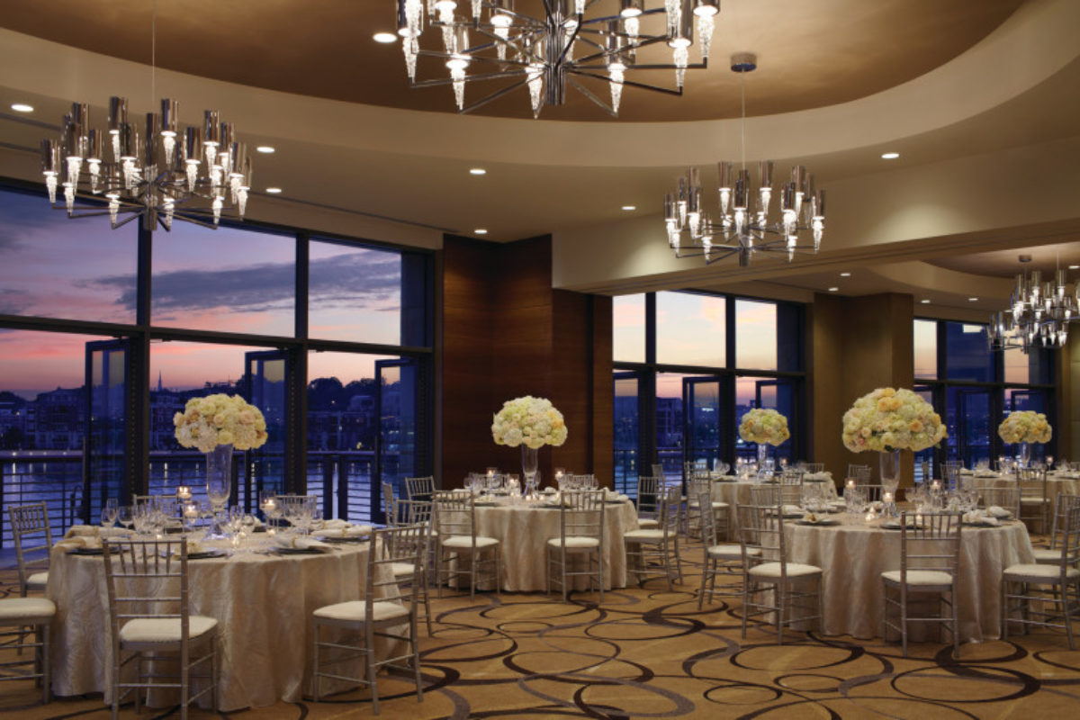 Ballroom decorated with white flowers with the sunset seen through the window.