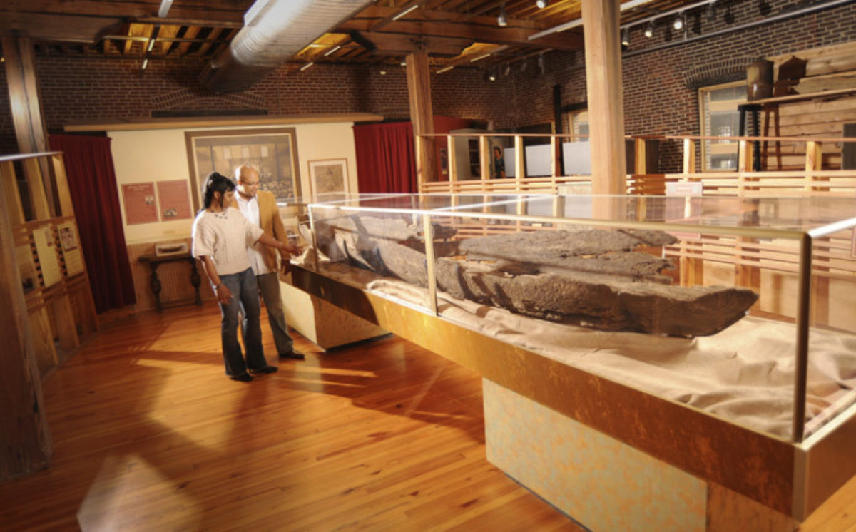 Visitors looking at the remains of a boat in a display case
