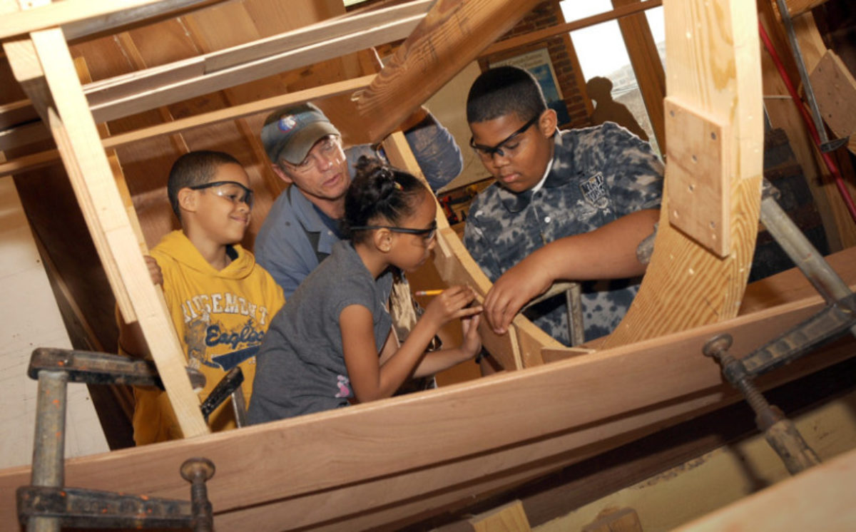Children making a wooden boat with an instructor.