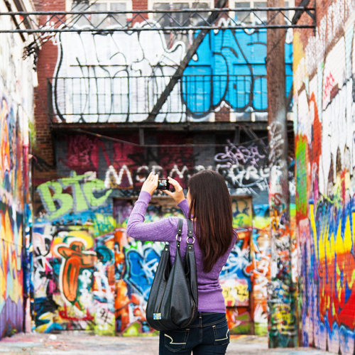 Woman takes photo of Graffiti Alley in Station North