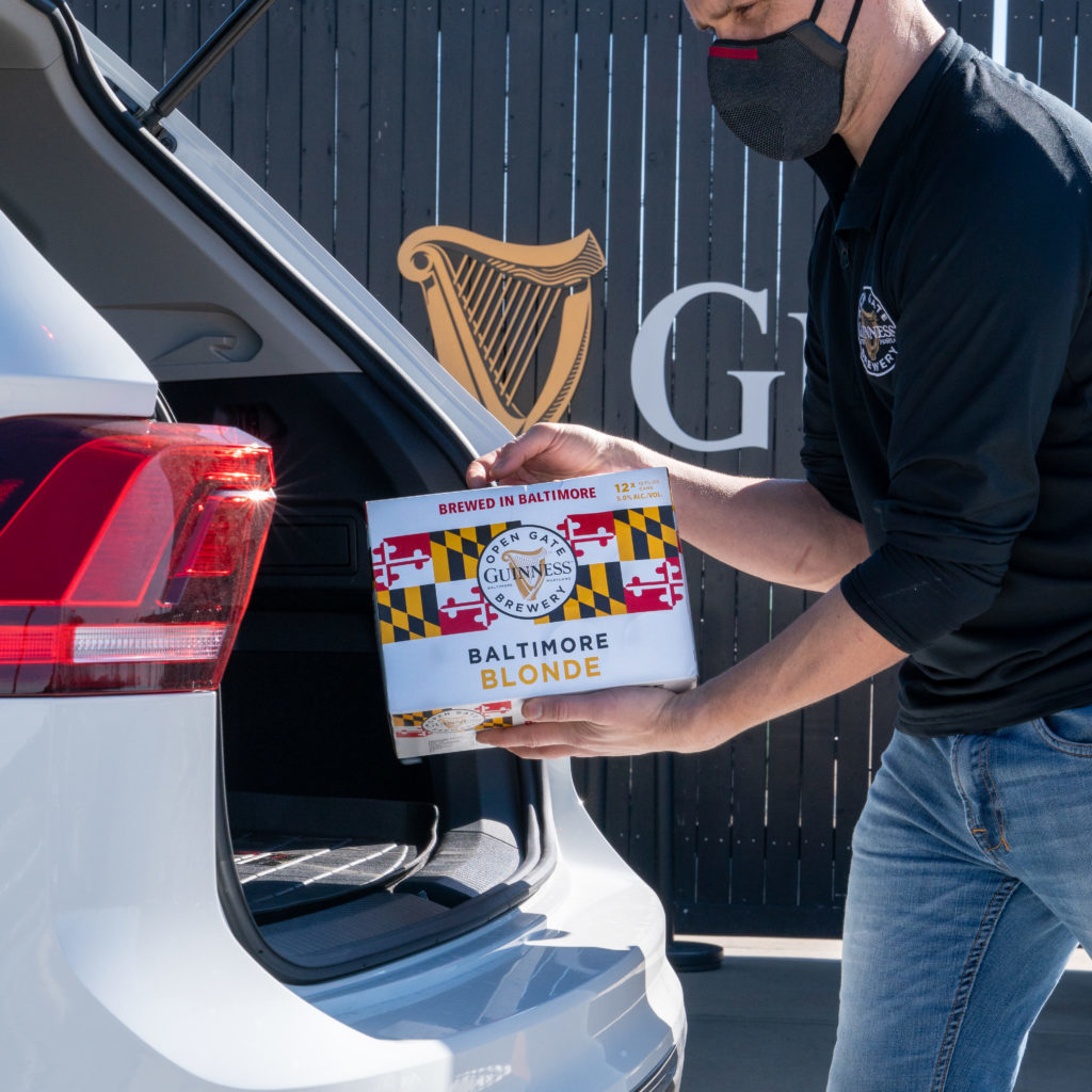 Person putting a case of beer in a car